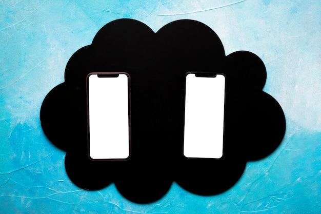 Два пустых мобильного телефона на черном облаке над окрашенной синей стеной