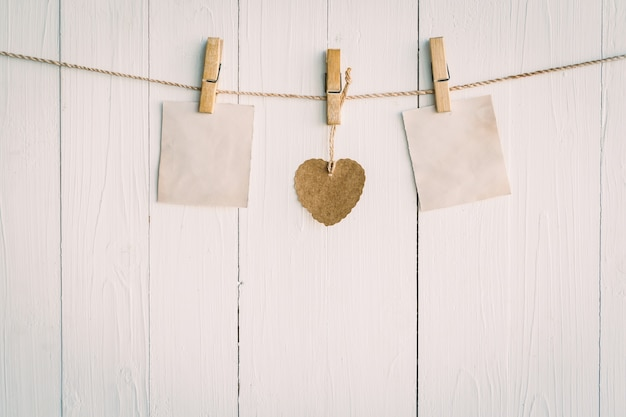 Two blank old paper and brown heart hanging. on white wooden background with vintage style.