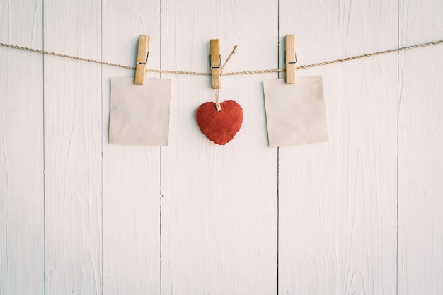 Two blank old paper and red heart hanging. on white wooden background with vintage style.