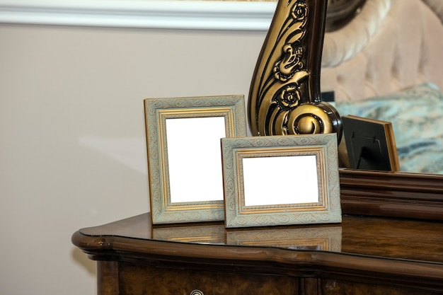 Two blank photo frame on the chest of drawers.