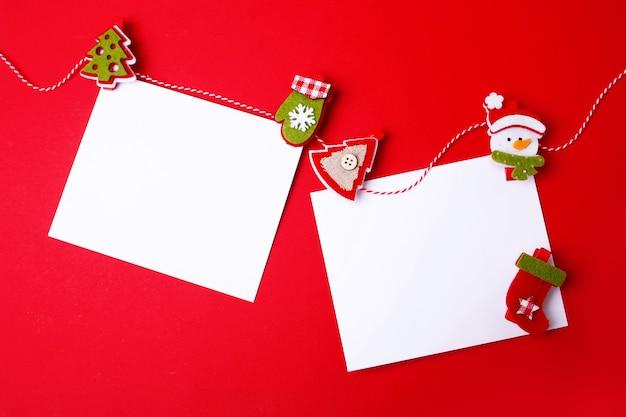 Два чистых листа и праздничные украшения на красном фоне. плоский стиль. пустое место.