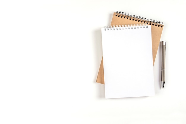 두 개의 빈 나선형 메모장이 자동 펜 옆에 있는 흰색 배경에 쌓여 있습니다. 흰색 및 재활용 시트가 있는 노트북. 교육, 사무실입니다.