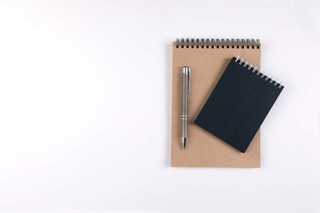 두 개의 빈 나선형 메모장이 자동 펜 옆에 있는 흰색 배경에 쌓여 있습니다. 검은색과 재활용 시트가 있는 메모장. 교육, 사무실입니다. 프리미엄 사진