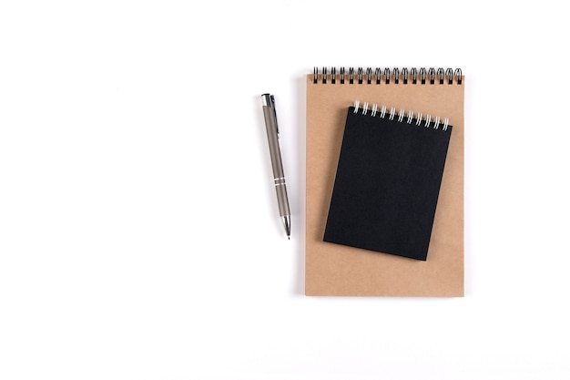 두 개의 빈 나선형 메모장이 자동 펜 옆에 있는 흰색 배경에 쌓여 있습니다. 검은색과 재활용 시트가 있는 메모장. 교육, 사무실입니다.