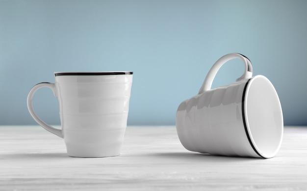흰색 테이블과 파란색 배경에 두 개의 빈 흰색 머그컵.