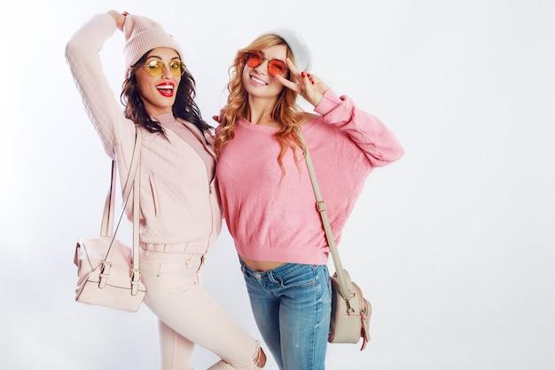 흰색 바탕에 스튜디오에서 포즈 핑크 유행 옷에 두 행복 한 여자. 재미, 걷기, 점프, 귀여운 친구