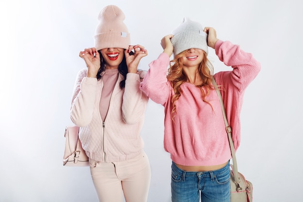 Two blissful girls in pink trendy  outfit   posing in studio on white background. cute friends having fun , walking, jumping,