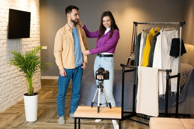 Два влиятельных блогера демонстрируют одежду своим подписчикам, чтобы продавать ее в интернет-магазине в помещении.