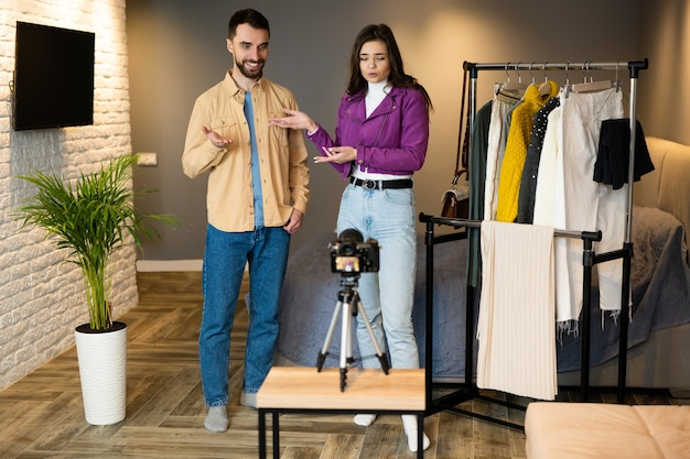 Два влиятельных блогера демонстрируют одежду своим подписчикам, чтобы продавать ее в интернет-магазине в помещении. Premium Фотографии
