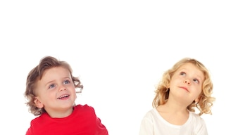 Two blond children looking up
