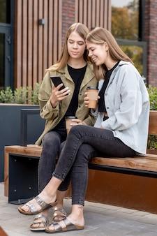 벤치와 화상 통화에 앉아 청바지와 재킷에 두 금발 소녀