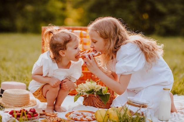 芝生の上に座ってピクニックをしている白い夏服を着た2人の金髪の姉妹。夏時間。