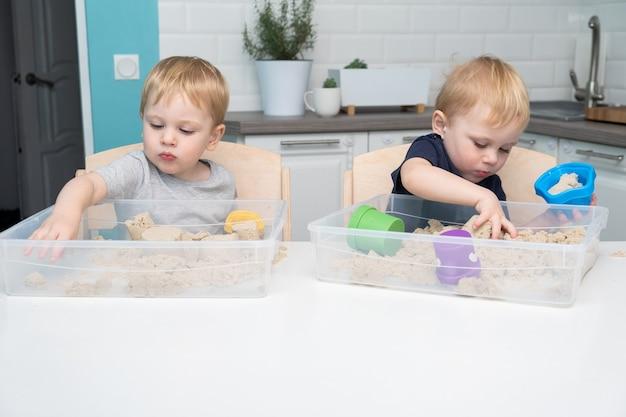 두 금발의 소년 쌍둥이 놀이와 운동 모래에 집