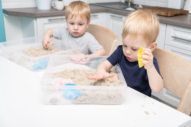 Two blonde boys twins play with kinetic sand at home