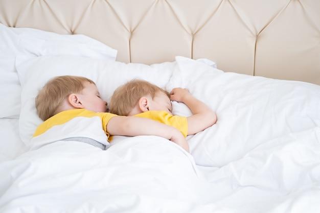 두 금발 소년 쌍둥이 흰색 침구에 포옹 자.