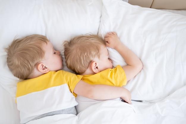 두 금발 소년 쌍둥이 흰색 침구에 껴안고 자.