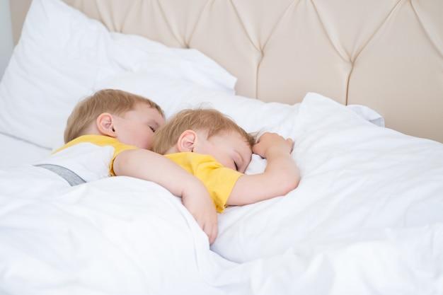 Two blonde boys twins sleeping hugging on white bedding