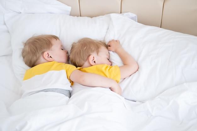 Two blonde boys twins sleeping hugging on white bedding .