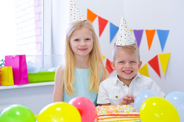 Two blonde caucasian kids boy and girl in birthday hats looking at camera and smiling at birthday party. colorful background with balloons and birthday rainbow cake.