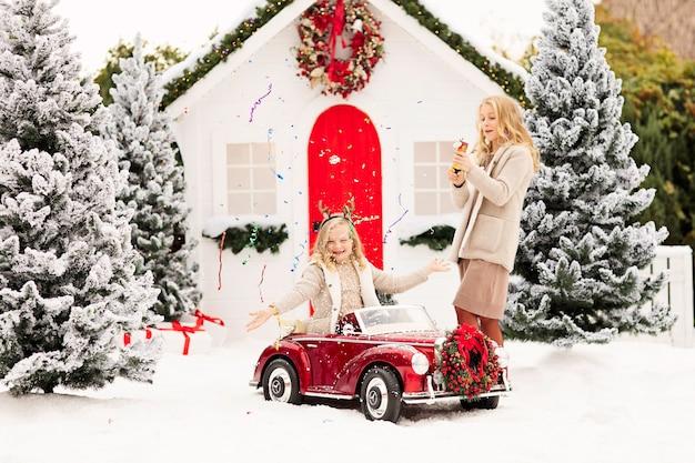 Две блондинки взрывают леденец возле снежных елок и белого рождественского домика.