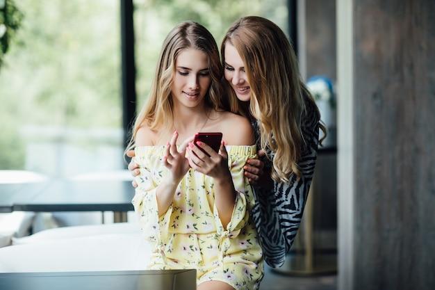 モダンなカフェのインテリアでスマートフォンと座っている2人の金髪の姉妹