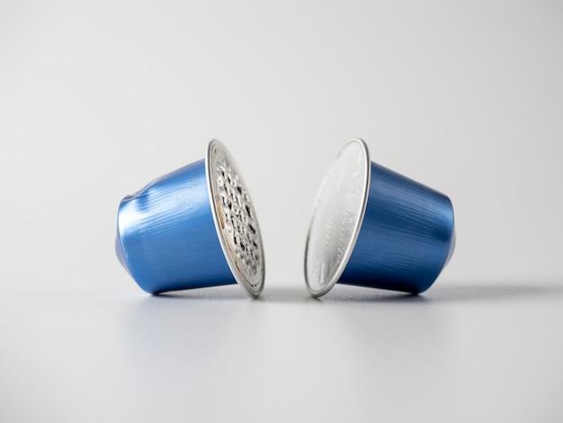 白い背景の上の挽いたコーヒーと2つの青いアルミニウムカプセル。それらの1つが使用されます。材料の保管と処理。環境にやさしい製品