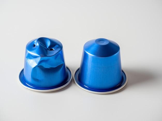 白い背景の上の挽いたコーヒーと2つの青いアルミニウムカプセル