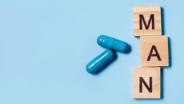 2つの青いカプセルと碑文の男。孤立した背景に男性の健康と性的エネルギーのための薬。勃起、効力の概念。男性の不妊症とインポテンツの治療。