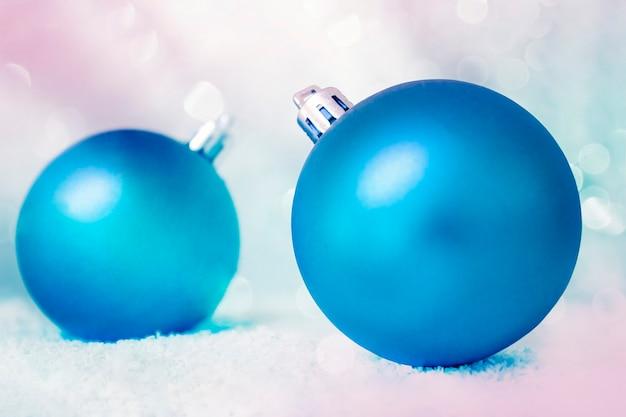 ボケとグラデーションで焦点がぼけた青い背景に雪の中で2つの青いクリスマスの装飾