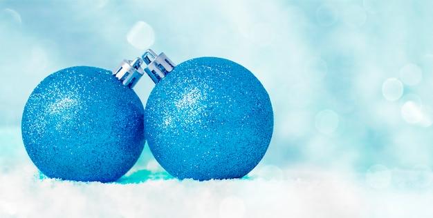 ボケ味の焦点がぼけた青い背景に雪の中で2つの青いクリスマスの装飾