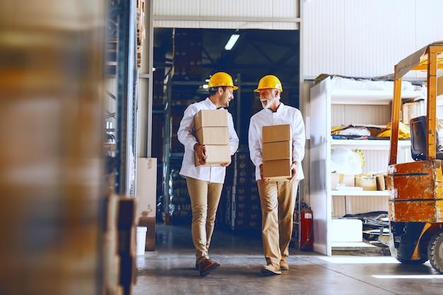 Два синих воротничка в белой форме и с желтыми касками на головах переносят тяжелые ящики на складе.