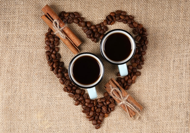 Two blue cups of coffee inside a heart shaped coffee beans on a burlap
