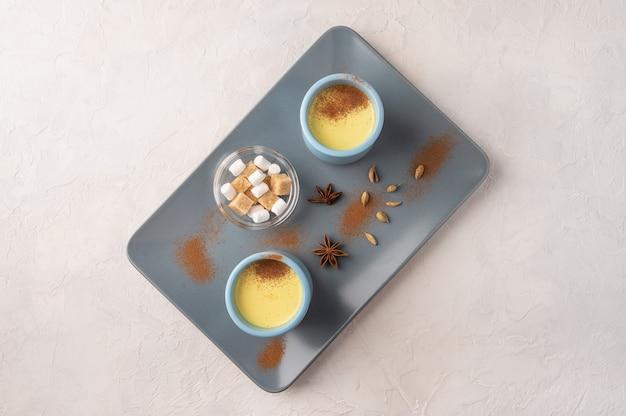 セラミックトレイにスパイスと砂糖で伝統的なインドのマサラチャイ茶と2つの青いカップ