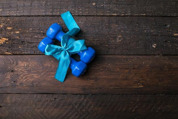 ギフトの弓と白紙のタグ、木の板にハート、スポーツホリデーコンセプトの2つの青いダンベル