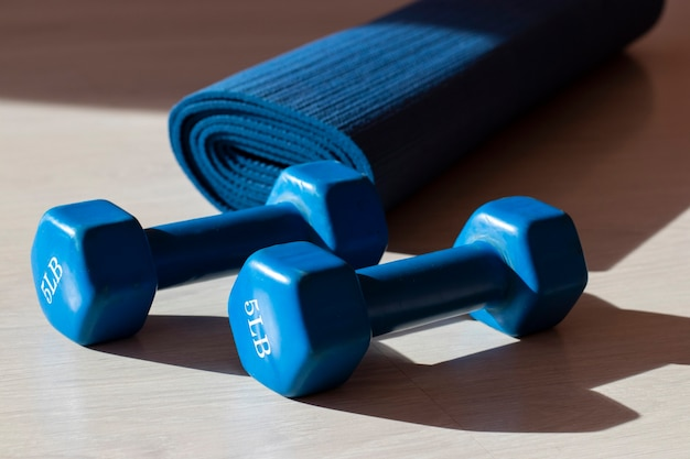 체육관에 그림자가 있는 두 개의 파란색 아령과 요가 매트. 스포츠 및 피트니스 개념