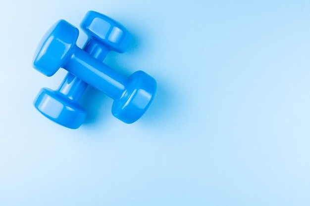 Two blue dumbbells on a blue background, photo banner, top view, space for text.