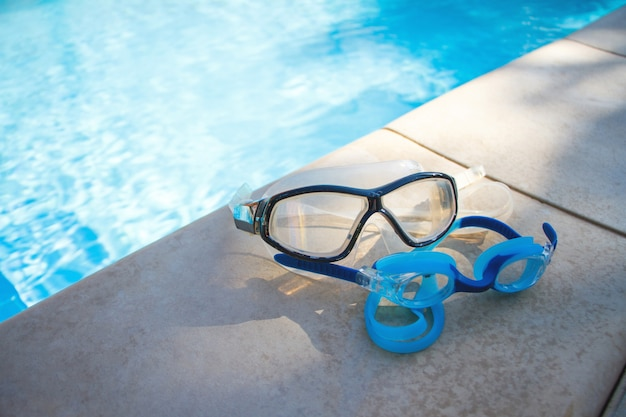 Two blue goggles for swimming lie on the side of the swimming pool on the background of crystal clear water