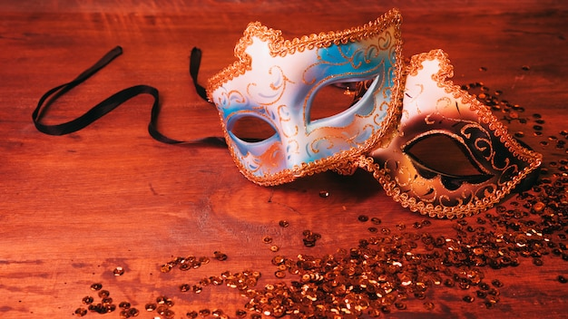 Two blue and golden carnival mask with glittering sequins on wooden desk