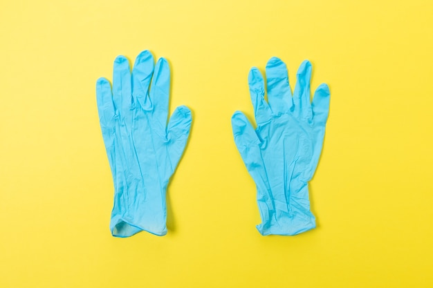 Two blue latex medical gloves on bright background.