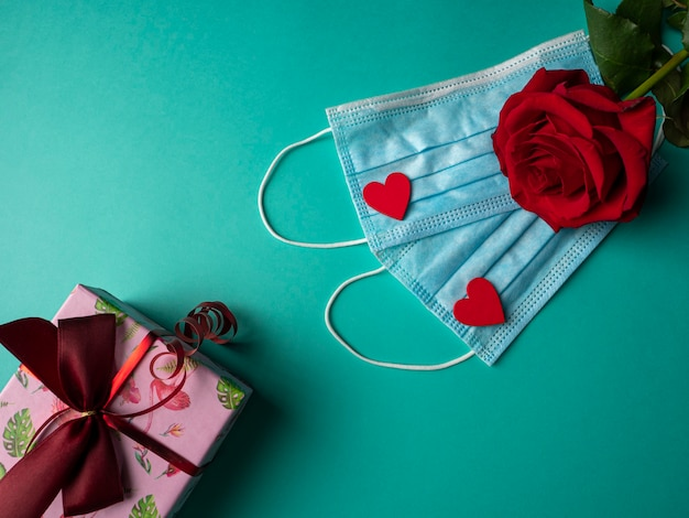 Two blue masks with two red hearts and a red rose on masks, and a pink gift on green