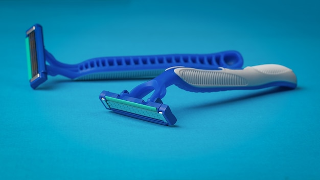 Two blue men's shaving machines on a blue surface. set for care of a man's face.
