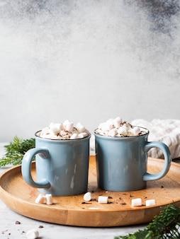 Две синие кружки с горячим шоколадом, взбитыми сливками, шоколадной стружкой на деревянный поднос на сером фоне. копировать пространство