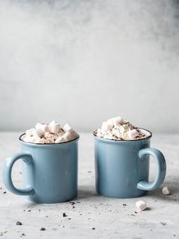 Две синие кружки с горячим шоколадом, взбитыми сливками, шоколадной стружкой на сером фоне. копировать пространство