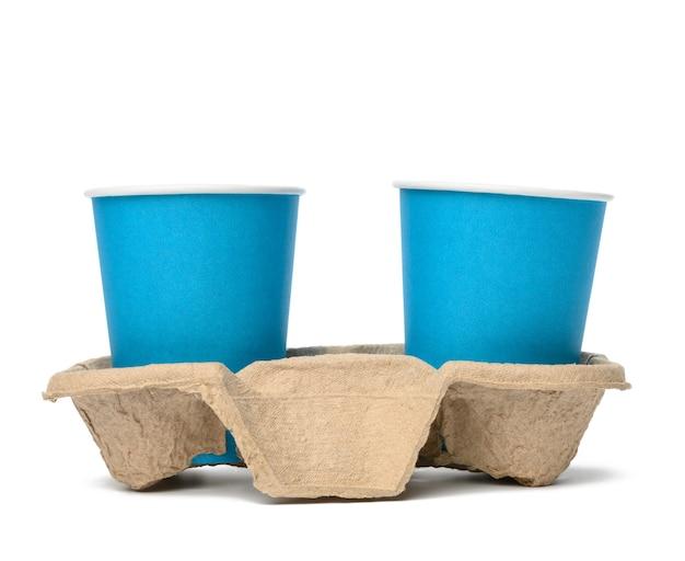 두 개의 파란색 종이 일회용 컵이 트레이, 흰색 배경, 테이크 아웃 용기에 서 있습니다.