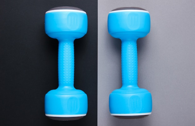Two blue plastic dumbbells on a gray-black table. top view