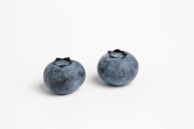 白い表面に分離された2つのブルーベリー