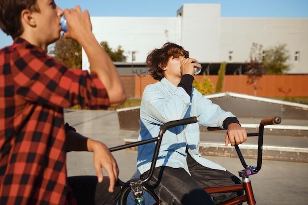 Два байкера bmx отдыхают в скейтпарке после тренировки. экстремальный велосипедный спорт, опасные велотренировки, уличная езда, езда на велосипеде в летнем парке