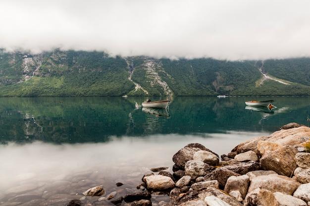 美しい山の湖の上の2つのボート 無料写真