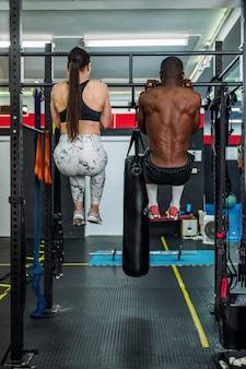 두 명의 보디빌더, 한 명의 흑인과 한 명의 백인이 스포츠 체육관에서 백 바벨 운동을 하고 있습니다. 체육관에서 몸을 강화하는 개념
