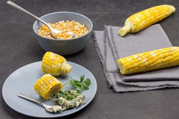 Два вареных початка на серой салфетке. кусочки вареной кукурузы, соус и ложка на серой тарелке. зерна кукурузы в миске. черный фон. вид сверху
